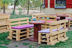 Wooden bench made of pallets for sitting with tables made from coil of electric cable Stock Photos