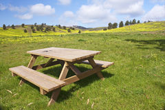 Wooden bench in the meadows. Garden wooden bench isolated in the green meadows Royalty Free Stock Photos
