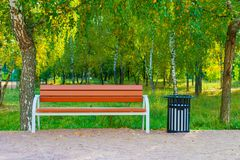 Wooden bench and trash can in the park. Wooden bench and metal black trash can in the park on a background of green trees Royalty Free Stock Image