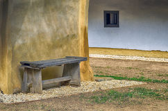 Wooden bench before a mud wall Stock Photography
