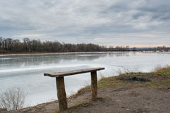 Wooden bench near the frozen river Stock Photo