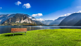 Wooden bench near the lake between by mountains Stock Photos