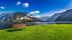 Wooden bench near the lake between by mountains Royalty Free Stock Photography
