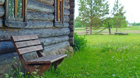 Wooden bench near old loghouse Stock Photos