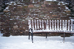 Wooden bench near a wall with snow. Wooden bench near a stone wall. They are covered with snow Royalty Free Stock Photography