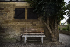 Wooden bench near the wall of a stone house with window shutters Stock Photos
