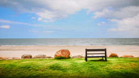 A Wooden Bench Near a White Sand Beach Looking to the Ocean Stock Photos