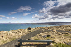Wooden bench next to a beautiful coast line in Iceland. Horizontal panorama of a wooden resting bench with a beautiful shoreline in the background and dramatic Stock Images