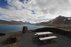 Wooden bench next to a beautiful lake panorama in Iceland Stock Photos