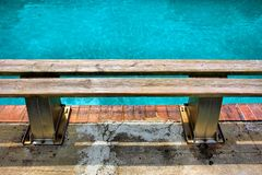 Wooden bench next to pool Stock Photos