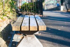 Wooden bench with no sitting people under sunlight feeling waiting moment. Wooden bench with no sitting people under sunlight feeling warm waiting moment stock photography