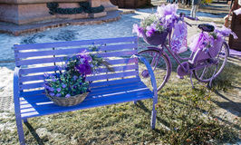 Wooden bench and old bicycle painted in purple. Wooden bench and old bicycle painted in purple and decorated with flowers and matching accessories royalty free stock photos