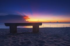 Wooden bench over beautiful tropical beach and magical twilight sunrise background Stock Image