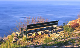 Wooden bench over the blue sea Stock Image