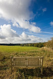 Wooden bench overlooking an English landscape. A single wooden bench overlooking a beautiful autumnal landscape in Warwickshire, England, with cloudy blue skies Stock Photography