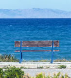 Wooden bench overlooking the sea and mountains. Old wooden bench overlooking the sea and mountains Royalty Free Stock Images