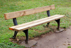 Wooden bench in the park on grass Stock Image