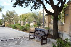 Wooden bench in park, malta, valetta,. With trees in background and stone wall Stock Image