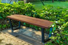 Wooden bench in the park at night with green tree surrounding Royalty Free Stock Photo