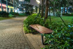 Wooden bench in the park at night with green tree surrounding Royalty Free Stock Images