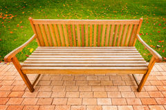 Wooden bench on the park road. Stock Image
