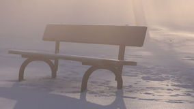 Wooden bench in park on snow and morning fog with sunlight