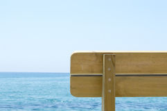 Wooden bench part with the  look at blue sea and horizon. Back of the wooden bench part with the  look at blue sea and the horizon Stock Images