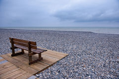 Wooden bench at a pebbles beach. On a cloudy day Stock Images
