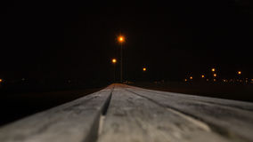 Wooden bench in perspective at night. Street lights on background royalty free stock photo