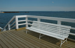 Wooden bench on pier. A white wooden bench on a wooden pier at the seaside Stock Images