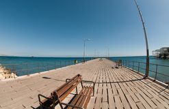 Wooden bench on the pier. Wooden bench on the pier at the port of Limassol Cyprus. Modern waterfront park with fountains and pools Royalty Free Stock Photos