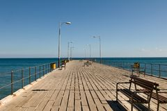 Wooden bench on the pier. Wooden bench on the pier at the port of Limassol Cyprus. Modern waterfront park with fountains and pools Stock Photos