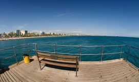 Wooden bench on the pier. Wooden bench on the pier at the port of Limassol Cyprus. Modern waterfront park with fountains and pools Stock Images