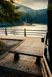 Wooden bench on the pier of a Synevyr lake. Synevir, Ukraine - OCT 20, 2008: wooden bench on the pier of a Synevyr lake. beautiful autumn evening stock photography