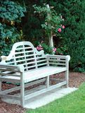 Wooden Bench And Pink Roses. Wooden bench and pink rose bush.Niagara Falls Botanical Gardens,Ontario,Canada stock photo