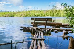 Wooden bench and a planked footway on a quiet pond. A fishing place stock photography