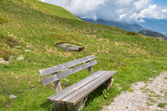 Wooden bench provided for hikers to rest while hiking at Zillert. Al Alps surrounded by mountains during summer in Tyrol, Austria, Europe Stock Image