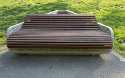 Wooden bench. In a public park, with a stone base Royalty Free Stock Images