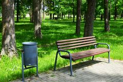 Wooden bench for rest and garbage can stock photo