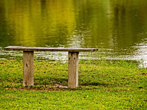 A wooden bench by the river Stock Image