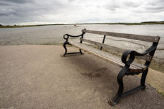 Wooden Bench and River Background. Single wood and cast iron metal bench with nobody in the scene with a water river based background Royalty Free Stock Photo