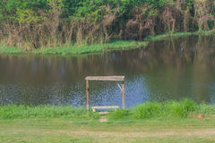Wooden bench with river and forest. Stock Photo