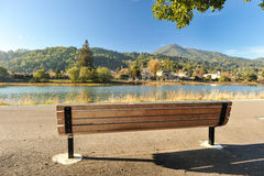 Wooden bench by a river with mountains Stock Image