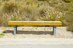 Wooden bench in a rural setting. Wooden bench on gravel stones in a rural setting on a hot summers day Stock Photo