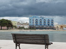 Wooden bench. On the seashore in Apulia, and a big hotel in the background Royalty Free Stock Photo