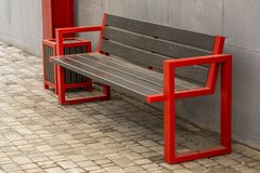 Wooden bench seat with handrails. Street wooden seat with red metal railing and a garbage can royalty free stock image