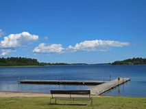 Wooden bench on the shore of Bia-Karen lake in Stockholm royalty free stock images