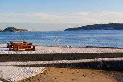 Wooden bench on the shore of the fjord Royalty Free Stock Photo