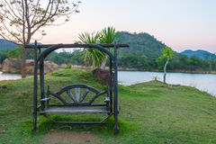 Wooden the bench on side of Lake and mountain, Thailand. Royalty Free Stock Photo