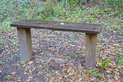 A wooden bench sitting in the woods Royalty Free Stock Image
